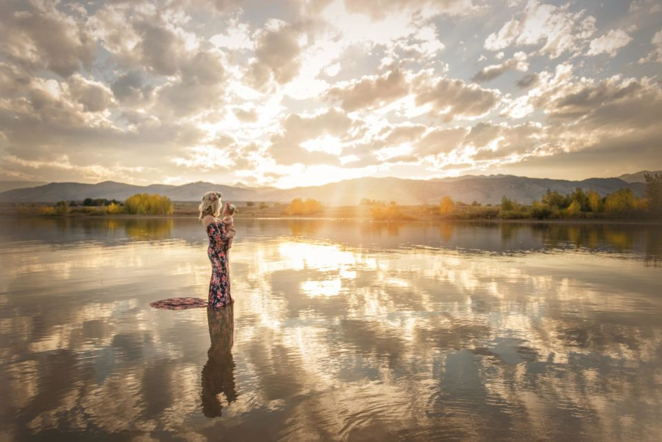 mother holding her baby girl standing in water at sunset - boulder photographer
