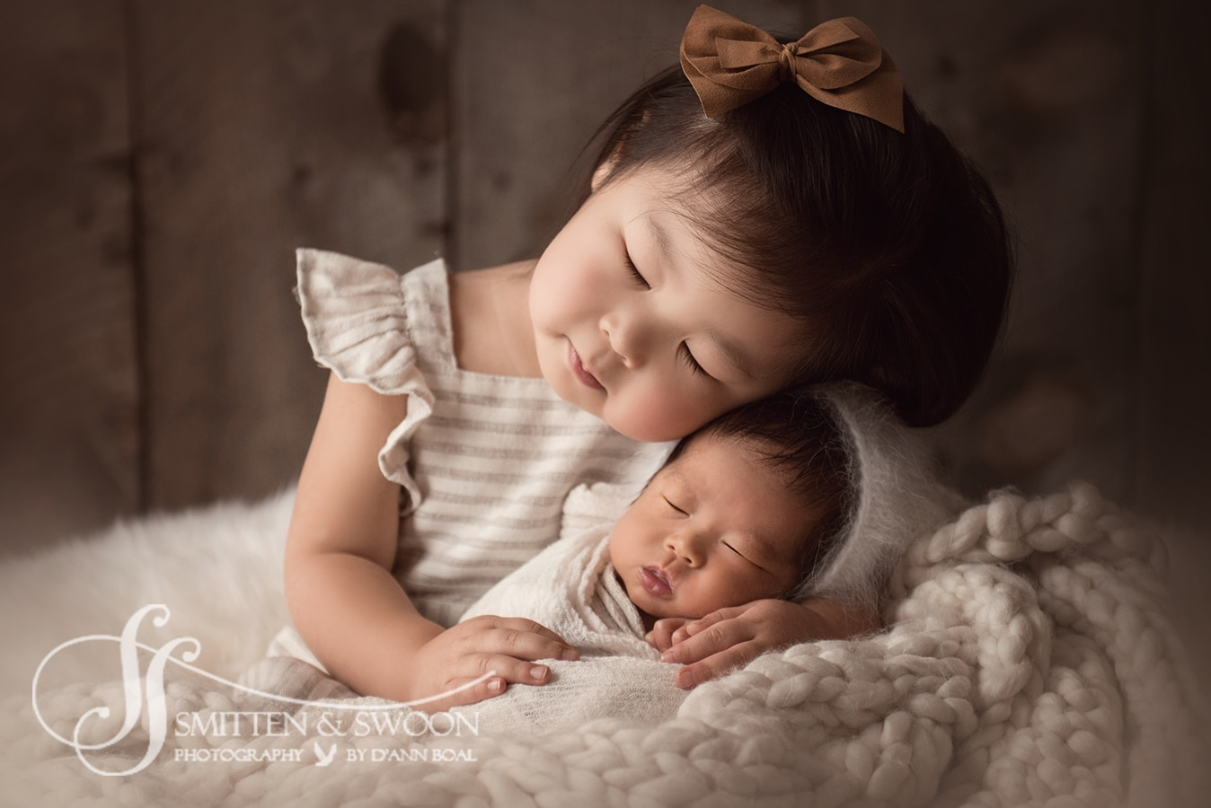 big sister holding newborn baby brother pose boulder photographer