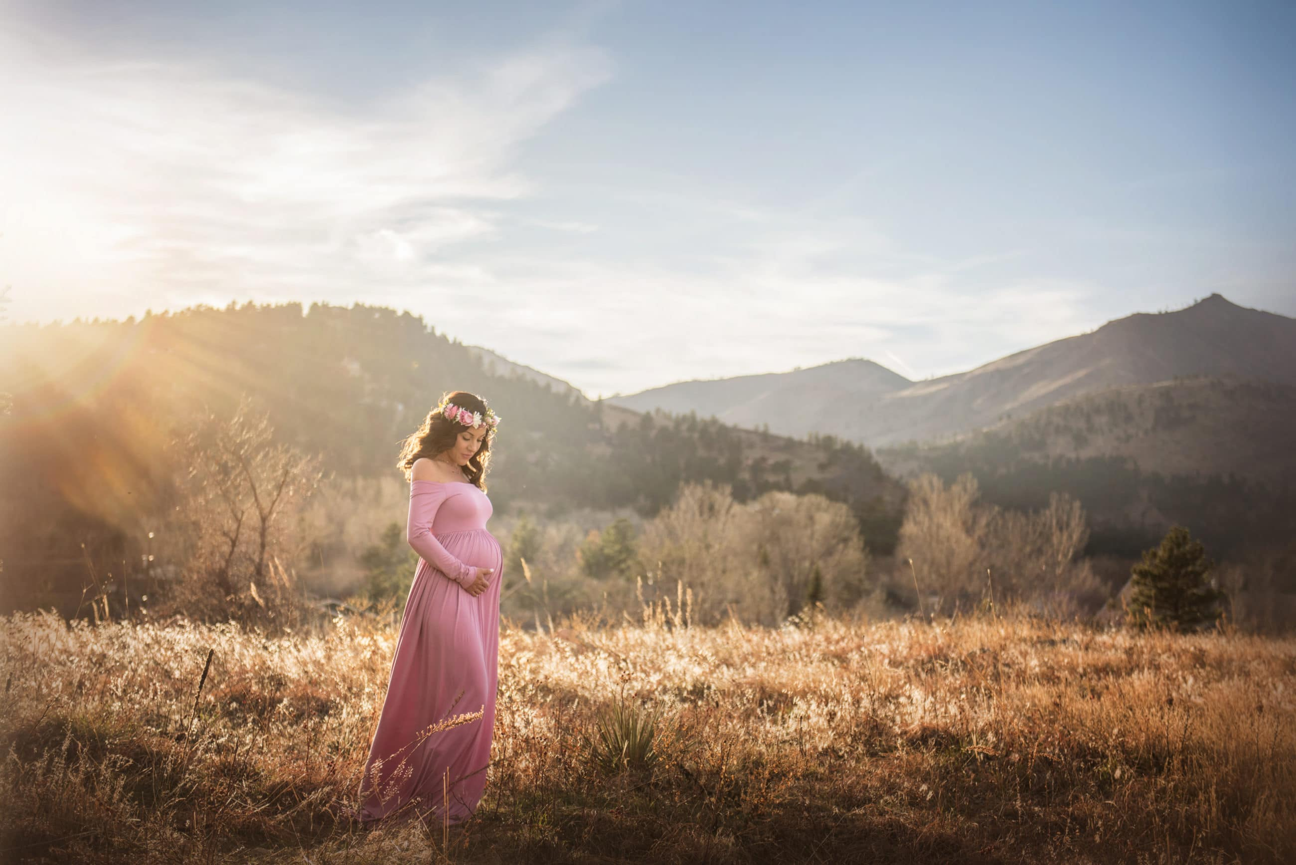pregnant mom in pink dress in golden field at sunset - baby's first year - boulder newborn photographer