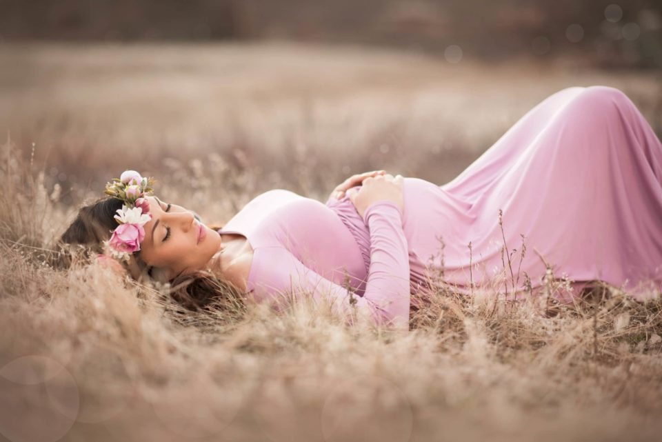 pregnant mother in pink maternity gown and flower crown laying down in golden grass - baby's first year - boulder newborn photographer