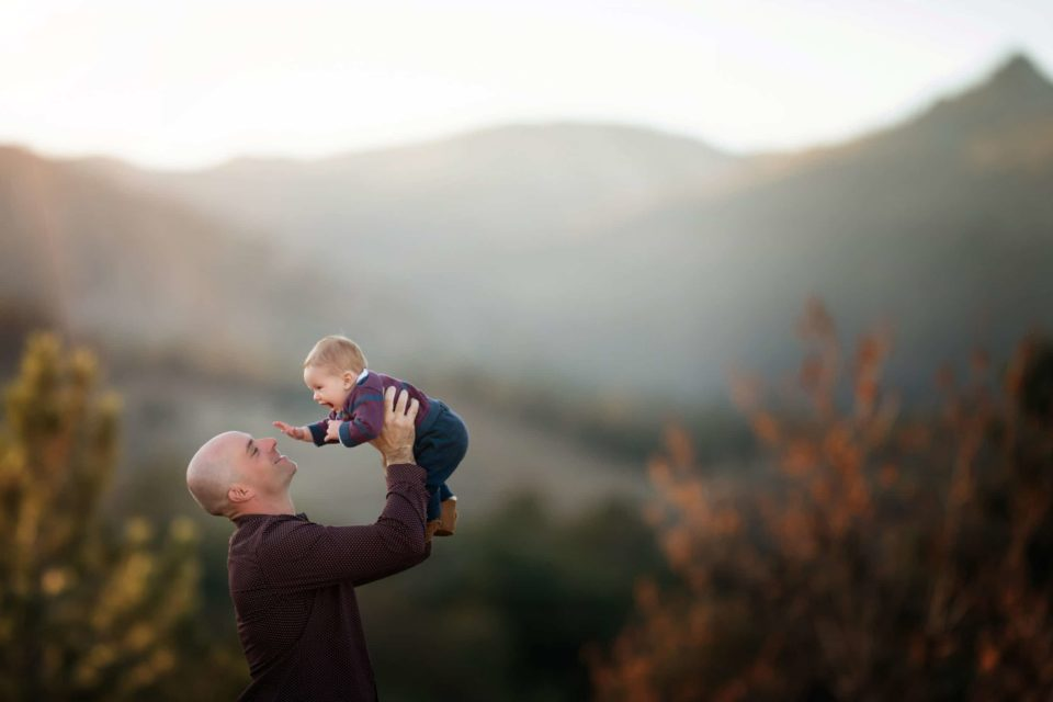 little boy in dad's arms fall foliage and mountain background - boulder photographer