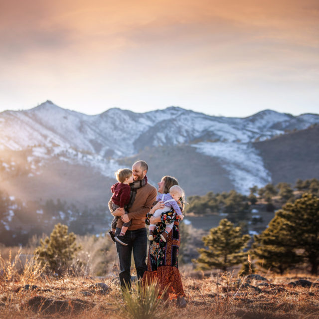 love and light - boulder photographer family of four hugging in field at sunset